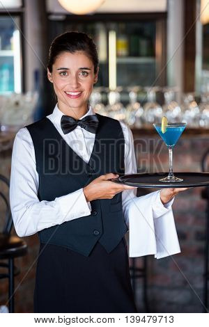 Portrait of female bartender holding serving tray with glass of cocktail