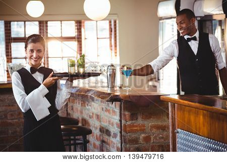 Portrait of female bartender holding a serving tray with two cocktail glass