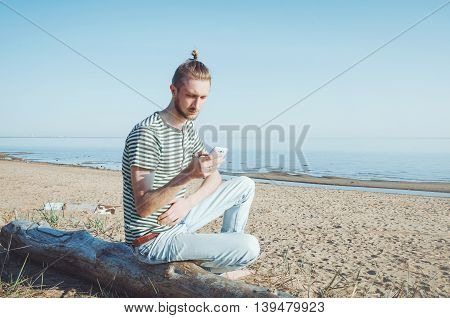 Portrait of stylish young man using smartphone sitting in autumn Baltic seaside outdoor. Serious bearded male with hairstyle hold phone and searh. Concept communication modern life. River coast.