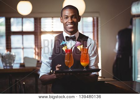 Portrait of bartender holding serving tray with two glass of cocktail