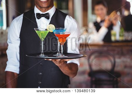 Mid section of bartender holding serving tray with cocktail glasses
