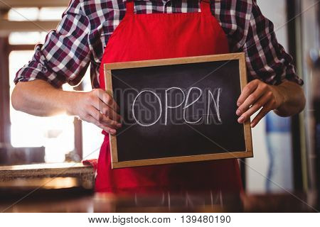 Mid section of waiter showing chalkboard with open sign at cafe