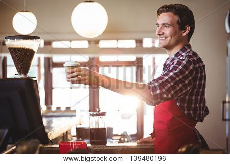 Smiling waiter offering a cup of coffee