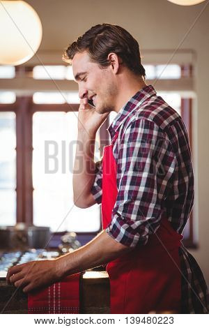 Waiter standing at counter talking on mobile phone