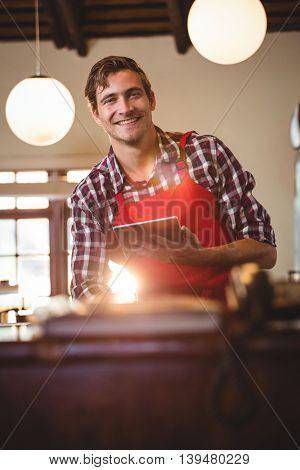 Portrait of smiling waiter standing at counter holding digital tablet