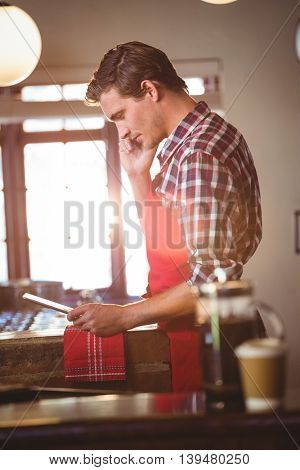 Waiter talking on mobile phone while using digital tablet at cafe