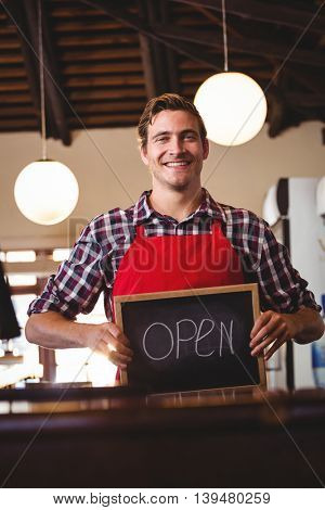 Smiling waiter showing chalkboard with open sign at cafe