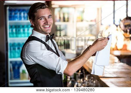 Portrait of smiling bartender cleaning wine glass at bar counter