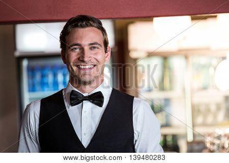 Portrait of smiling bartender standing at bar