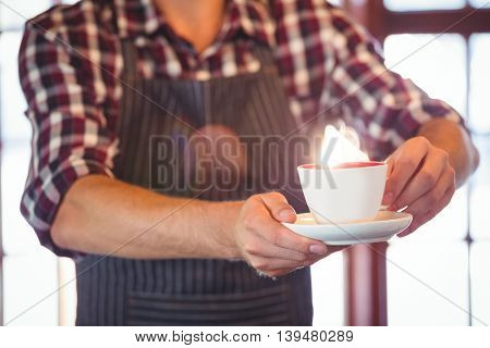 Mid section of waiter serving a cup of coffee at cafe