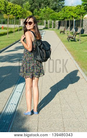 Girl Smiling In Park Wearing Summer Dress And Backpack