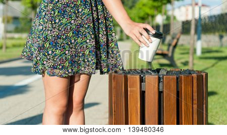 Female Hand Throwing Paper Cup On Trash In Park
