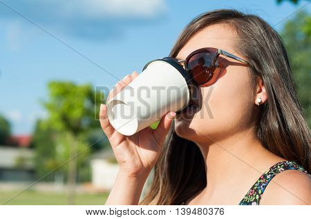 Close-up Of Woman Drinking  Takeaway Coffee Outside In Park