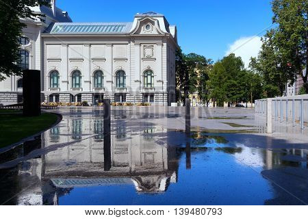 The building of the renovated National Museum of Art in Riga with reflection in puddles after rain