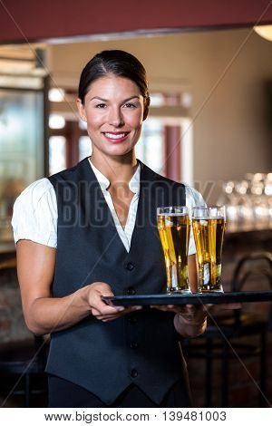 Portrait of smiling waitress holding serving tray with two glass of beer