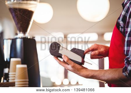 Mid section of waiter standing at counter using credit card machine