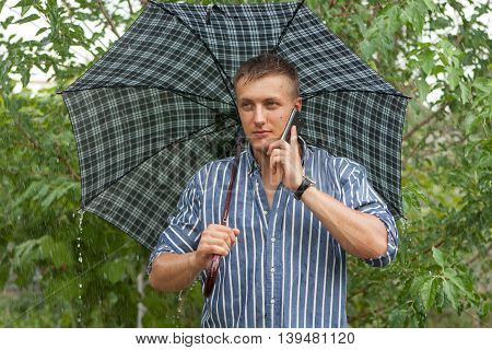 Man With Umbrella And Mobile Phone