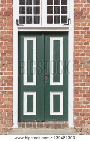 Old wooden door of a brick house, dutch style