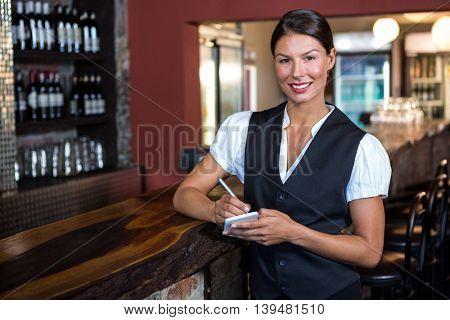 Portrait of smiling waitress taking order in restaurant