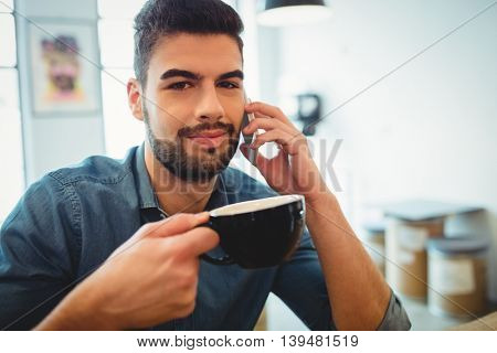 Man talking on mobile phone while having coffee in office cafeteria