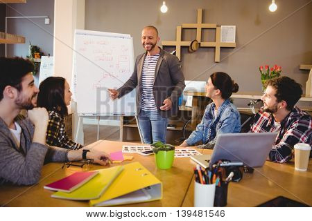Male graphic designer discussing chart on white board with coworkers in the office