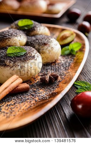 Traditional sweet steamed dumplings with a plum jam, sprinkled with ground poppy seeds on a wooden plate and background