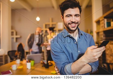 Portrait of graphic designer text messaging on mobile phone while colleagues interacting in background