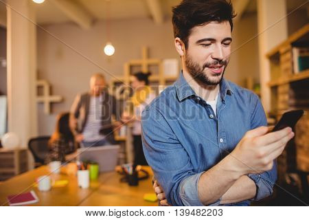 Graphic designer text messaging on mobile phone while colleagues interacting in background
