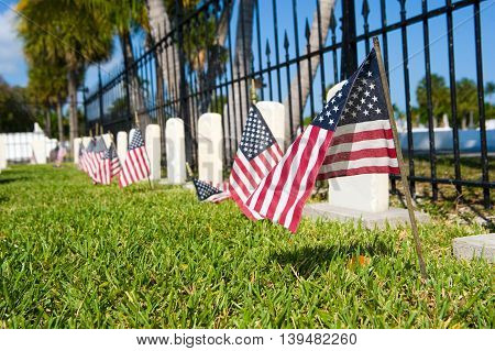 KEY WEST FLORIDA USA - MAY 02 2016: American flags on graves at the battleship Maine memorial section at the Key West cemetery.