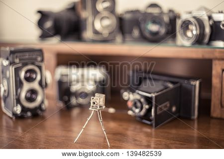Silver model of vintage photo camera with many different out of focus camera in background on collector desktop