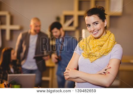 Portrait of graphic designer with arms crossed while colleagues interacting in background