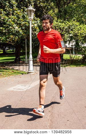 Urban athlete running through the park is dressed in a red shirt and black shorts, the image has a moving fast effect