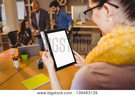 Close-up of graphic designers using digital tablet while colleagues interacting in background