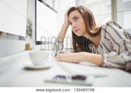 Tired businesswoman looking at computer in creative office