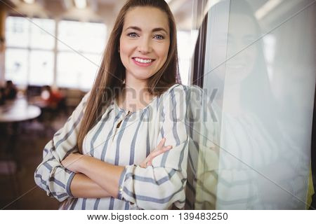 Portrait of smiling businesswoman with arms crossed in office cafeteria