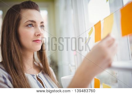 Young businesswoman looking at adhesive notes on window in creative office