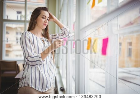 Thoughtful young businesswoman holding adhesive note by glass window in creative office