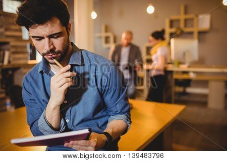Graphic designer reading notes from his diary in office