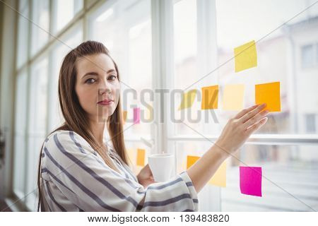 Portrait of young businesswoman touching adhesive notes while having coffee in creative office