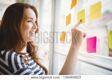 Happy young businesswoman touching adhesive notes on window in creative office