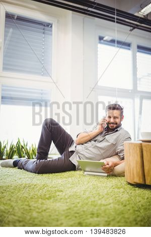 Portrait of happy businessman talking on phone while using laptop at creative office