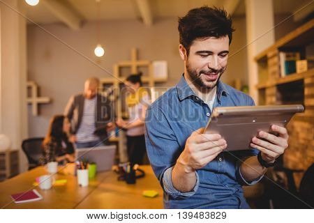 Graphic designer using digital tablet while colleagues interacting in background