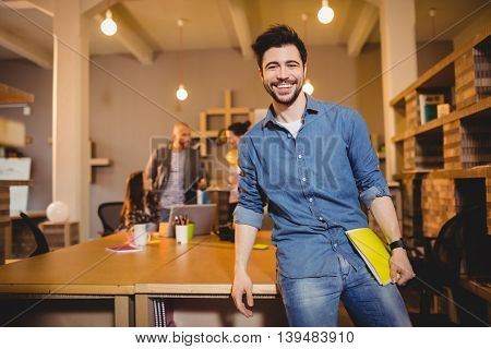 Portrait of graphic designer holding file while colleagues interacting in background