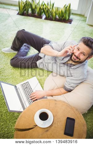 High angle portrait of happy businessman using laptop and mobile phone at creative office