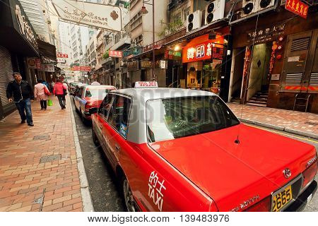 HONG KONG, CHINA - FEB 12, 2016: Taxi cars waiting for the passengers on busy city street with many stores on February 12 2016. There are 1223 skyscrapers in Hong Kong.