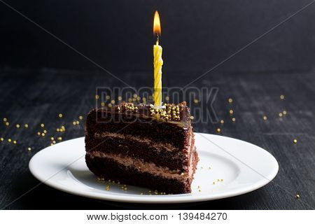 a piece of festive chocolate cake with a candle on a dark background
