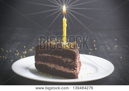 a piece of festive chocolate cake with a candle on a dark background,toned image