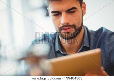 Close-up of young man using digital tablet in office cafeteria