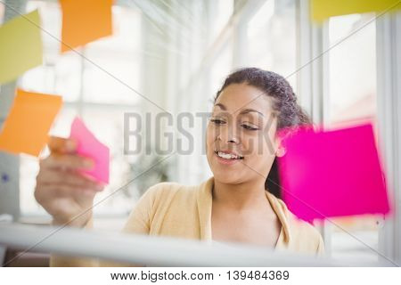 Young businesswoman sticking adhesive notes on glass window in creative office