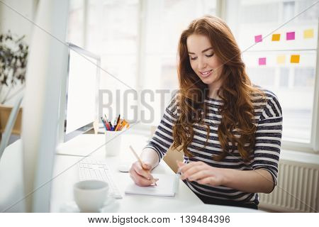 Happy young businesswoman working in creative office